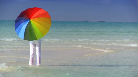 koruma : Serene young female with a parasol of rainbow colors on a beautiful white sandy beach Stok Video