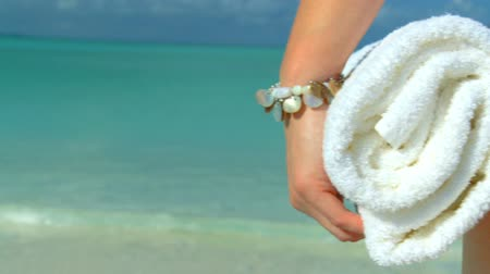 towel : Elegant young female in swimwear  on a beautiful white sandy beach looking at aquamarine waters 60 FPS