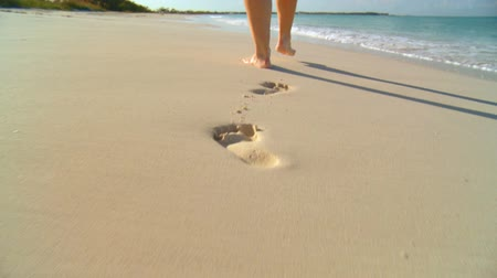 ślady stóp : Young caucasian girl leaving footprints in the white sand of a tropical beach 60 FPS