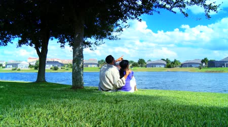 casal heterossexual : Young african american couple relaxing by a lake planning their future lifestyle
