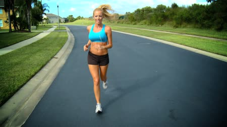 subúrbio : Beautiful blonde female enjoying jogging along suburban roads in the sunshine 60 FPS