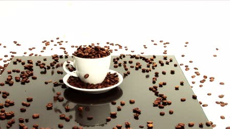 bögre : Coffee beans pouring into white coffee cup  & saucer