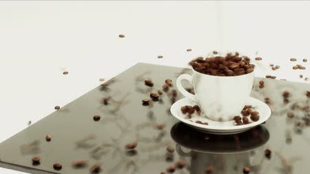 rozlití : Coffee beans pouring into white coffee cup  & saucer