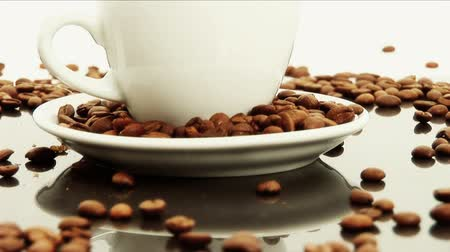 coffee brewing : Coffee beans overflowing from white coffee cup