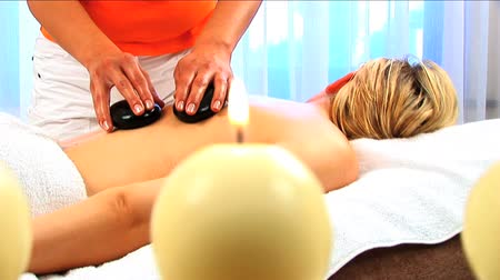 kamień : Blonde girl has hot stone massage with candles burning in the foreground Wideo