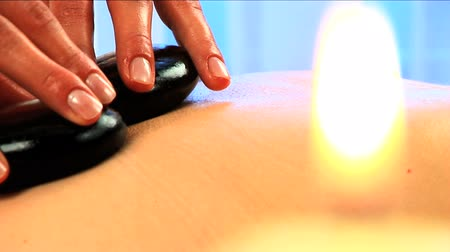 massages : Blonde girl has hot stone massage in close-up with candles burning in the foreground Stock Footage