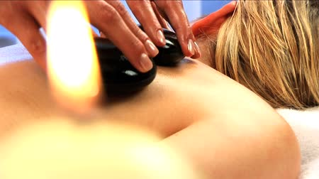 estância termal : Blonde girl has hot stone massage with candles burning in the foreground Vídeos