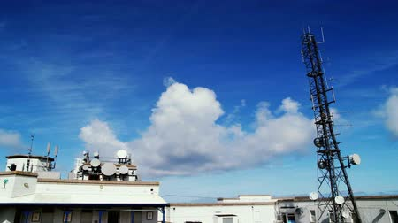 telekomünikasyon : Communications tower and station time-lapse with clouds and blue sky