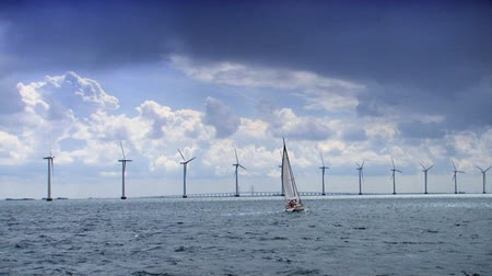 türbin : Yacht sailing past a row of wind turbines off the coast of Denmark