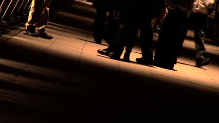pedestrian only : Lower limbs only of people walking on sidewalk at night in shadow