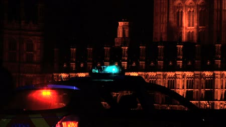 polícia : Police and ambulance car lights flashing at night, Houses of Parliament in the background Stock Footage