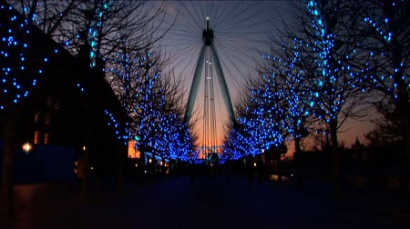 winter place : London Eye at night surrounded by Christmas light decorations Stock Footage