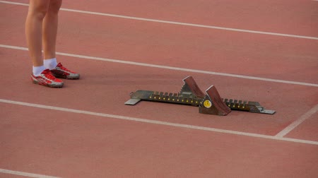 гонка : legs girls athletes and starting blocks on track stadium. before start of sprint race