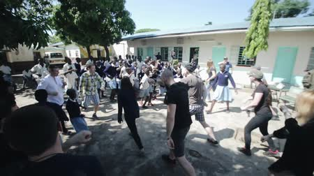 oportunidade : KISUMU,KENYA - MAY 15, 2018: Crowd dancing outside in summer. Men, women and kids having fun together in Africa.