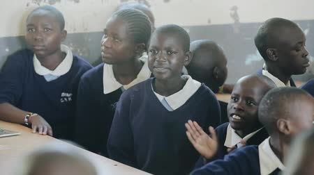 third world : KISUMU,KENYA - MAY 15, 2018: Group of african children sitting in classroom and looking at camera. Little boy clap hands. Stock Footage