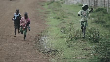 barefooted : KISUMU,KENYA - MAY 15, 2018: Three African children are running along the road. Girl and boys playing outside.