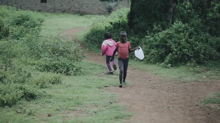 deprived : KISUMU,KENYA - MAY 15, 2018: Two african kid walking in the forest together. Happy boy and girl spending time outside.