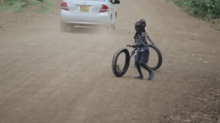 deprived : KISUMU,KENYA - MAY 15, 2018: Two african boys playing with tires on the road. Kids having fun together. Stock Footage