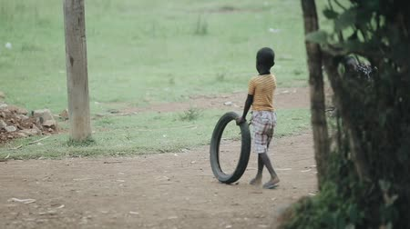 third world : KISUMU,KENYA - MAY 15, 2018: View through leafs of african boys playing with tires on the road. Kids having fun together.