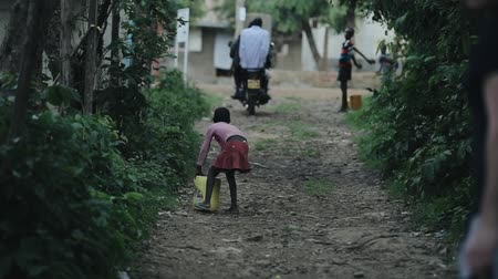 deprived : KISUMU,KENYA - MAY 17, 2018: Back view of african girl carrying the canister with water. kid walking through road village. Stock Footage
