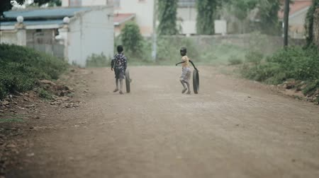 deprived : KISUMU,KENYA - MAY 17, 2018: Back view of two african boys running through road and playing with car tire in village.