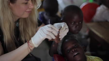 notas : KISUMU,KENYA - MAY 24, 2018: Caucasian woman helping children from Africa. Female cutting their nails with scissors. Stock Footage