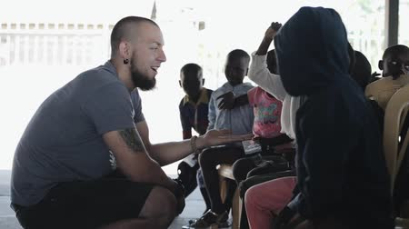 notas : KISUMU,KENYA - MAY 19, 2018: Group of children from Africa give five to caucasian man, volunteer and kids have fun.
