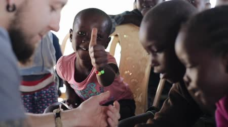 notas : KISUMU,KENYA - MAY 19, 2018: Group of little happy children from Africa and caucasian volunteer in poor village.