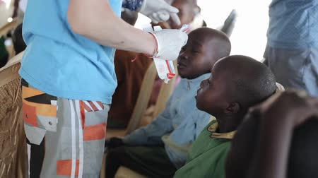 third world : KISUMU,KENYA - MAY 19, 2018: Caucasian man in gloves drawing african children sores on the head with medicinal salve.
