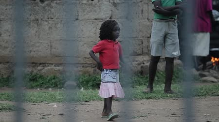 deprived : KISUMU,KENYA - MAY 23, 2018: View through the fence. Group of african people spending time outside. Little girl having fun.