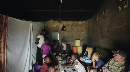 fome : KISUMU,KENYA - MAY 23, 2018: Camera moves down. Group of volunteers came to African family and sits at table, talking
