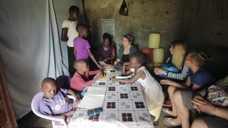 sourozenci : KISUMU,KENYA - MAY 23, 2018: Big group of people sitting in poor house of African family. Caucasian men and women talk Dostupné videozáznamy