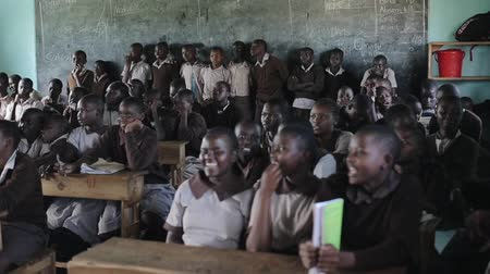 fome : KISUMU,KENYA - MAY 21, 2018: View of the large classroom full of African children. Boys and girls smile and stand up.