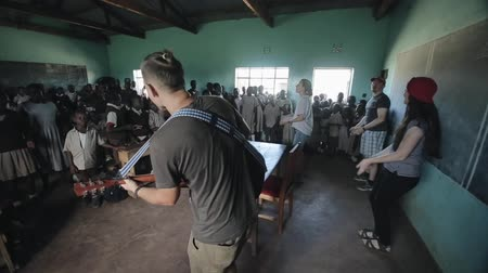 crowd together : KISUMU,KENYA - MAY 21, 2018: Group of african children singing and dancing in classroom with caucasian volunteers with guitar.