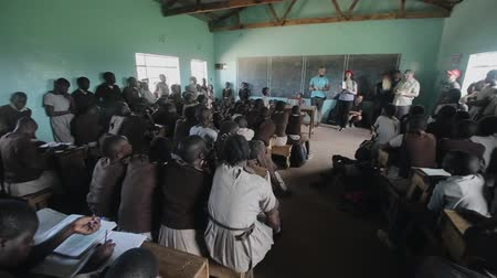 notas : KISUMU,KENYA - MAY 21, 2018: Group of Caucasian volunteers at small school in Africa. Children listen in a classroom. Stock Footage