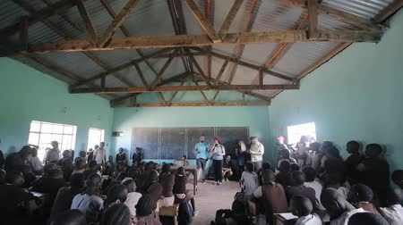 fome : KISUMU,KENYA - MAY 21, 2018: Camera moves down. Caucasian volunteers talk at school in Africa. Children sit in classroom. Vídeos