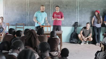 yoksulluk : KISUMU,KENYA - MAY 21, 2018: Group of Caucasian people, volunteers in African school, talk with children, tell something