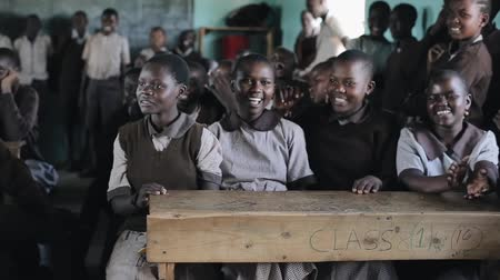 third world : KISUMU,KENYA - MAY 21, 2018: Group of happy African children sitting in classroom and smiling, laughing together.