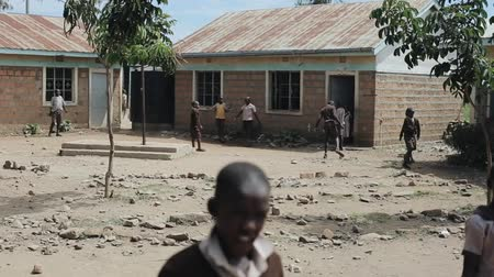 fome : KISUMU,KENYA - MAY 15, 2018: Group of African children in uniform playing football in the school yard. Poor village in Africa.
