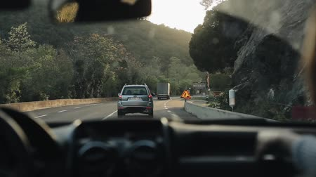 navíjení : Barcelona, Spain - April 27, 2018: Rear view of a lorry and a car going down the curvy mountain road while the sun is shining brightly Dostupné videozáznamy