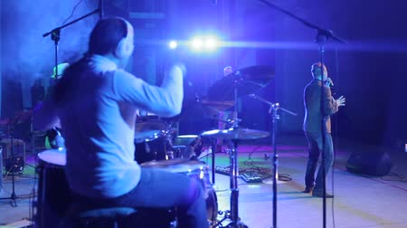 bas : Bobruisk,Belarus - JULY 31, 2018: A back view of a singer performing on stage and a drummer playing the drums Dostupné videozáznamy
