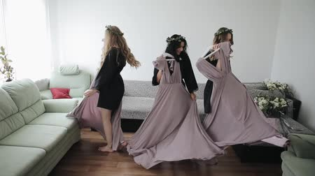 getting ready : Minsk, Belarus - June 30 2018: Tree beautiful bridesmaids are turning around holding their fancy dresses Stock Footage