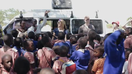 girl claps : KENYA, KISUMU - MAY 20, 2017: African children in uniform spending time with Caucasian women and man outside.