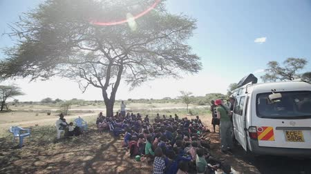 três : KENYA, KISUMU - MAY 20, 2017: African children sitting on the ground near tree and listen to Caucasian men and women. Stock Footage
