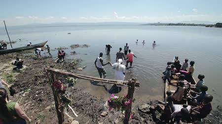 baptism : KENYA, KISUMU - MAY 20, 2017: African people come into the water in clothes, celebrating baptizing in the lake. Stock Footage
