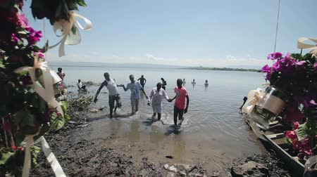 baptism : KENYA, KISUMU - MAY 20, 2017: African people go out of the water on the lake shore on a sunny summer day. Stock Footage