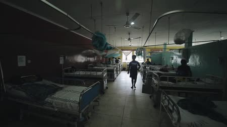 admission : KENYA, KISUMU - MAY 20, 2017: African woman walking through the room full of people in little hospital in Africa.
