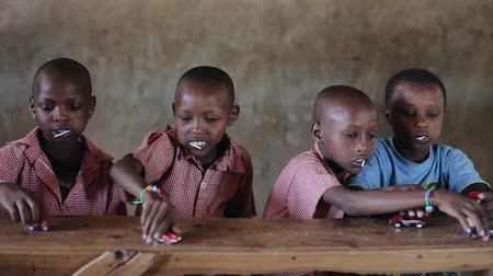 três : KENYA, KISUMU - MAY 20, 2017: Bald beautiful African boys sitting at the table and playing with toys, cars. Stock Footage