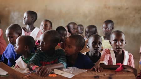 três : KENYA, KISUMU - MAY 20, 2017: Beautiful small children sitting at the tables in local school on Africa. Stock Footage