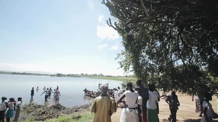 batismo : KENYA, KISUMU - MAY 20, 2017: Big group of African people staying on the shore and in the lake in sunny day.